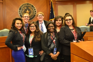 A group of young adults participating in the Youth and Government conference pose in a courtroom