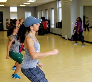 An instructor leads a group in Zumba exercise & dancing.
