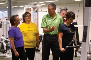 A group of adult cancer survivors work out with the help of a trained coach.