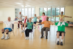 A group of adults does coordinated arm stretches, some are seated, some are standing.