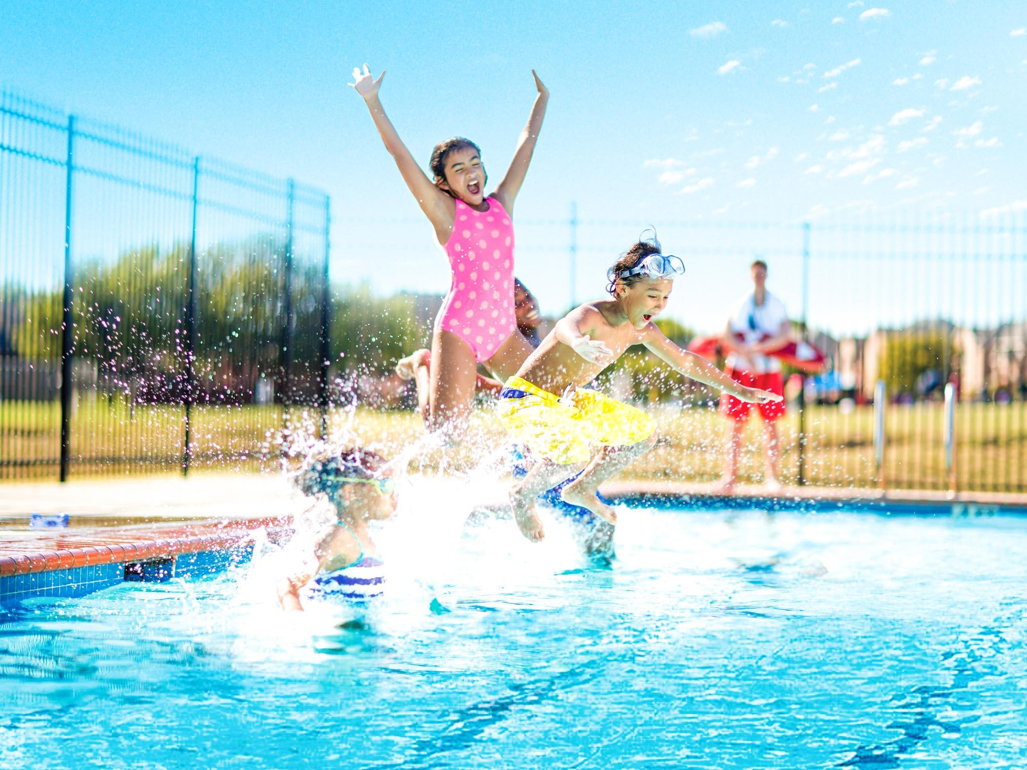 Kids jump into outdoor pool