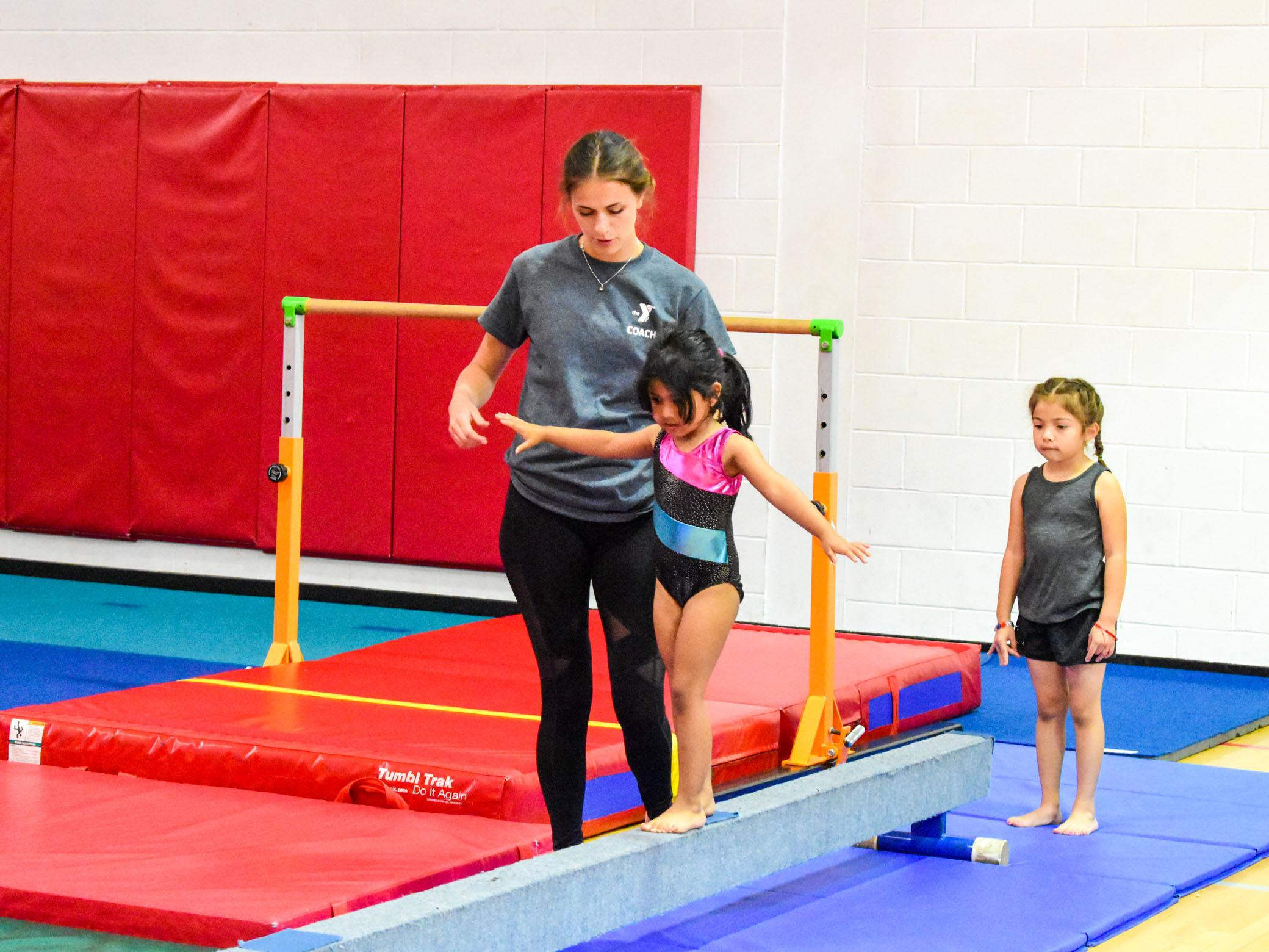 Instructor helps kids in youth gymnastics class