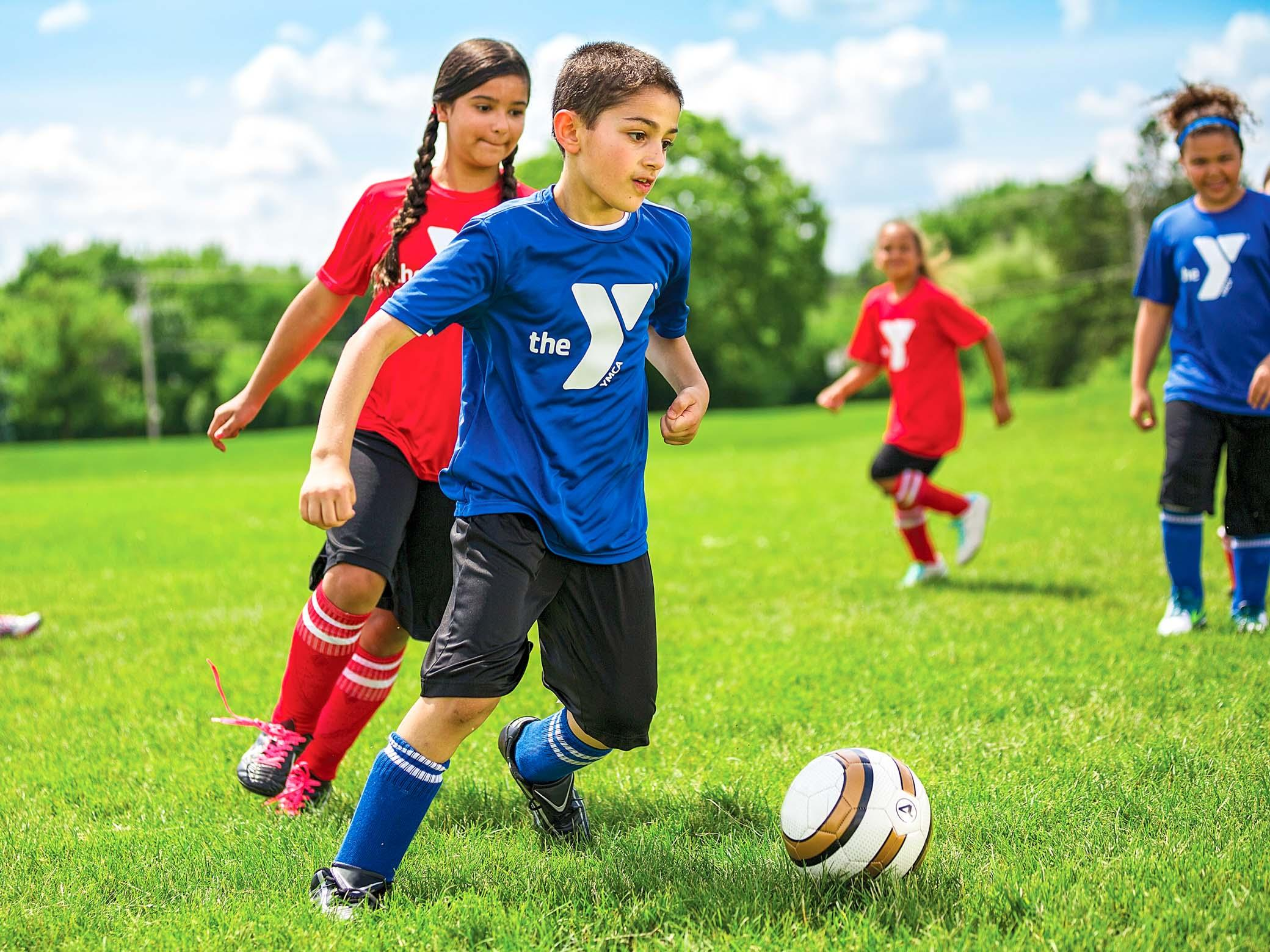 Children play soccer game wearing YMCA shirts