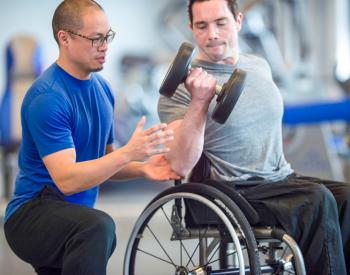 Fitness trainer helps man with weights