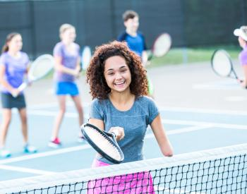 Woman with one arm plays tennis at YMCA