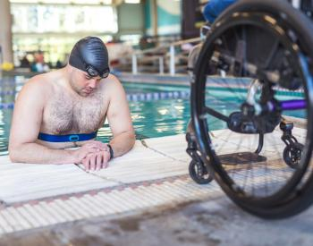 Man in pool behind wheelchair
