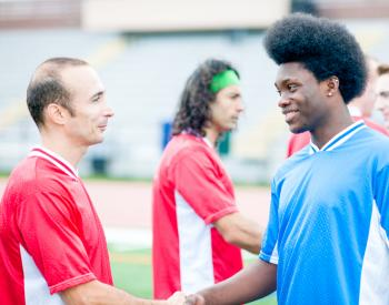 Men shake hands during soccer game