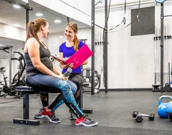 Trainer helps woman at gym