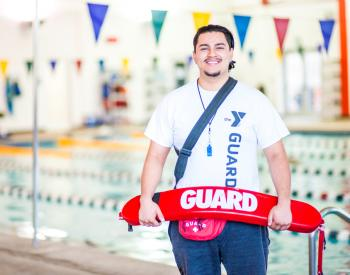Lifeguard stands in front of indoor pool