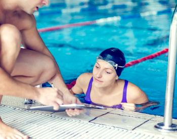Woman in pool looks at trainer's clipboard