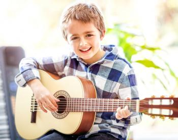 Smiling young boy holds guitar