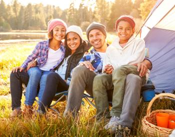 Smiling family sits in front of tent