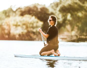 Woman in sunglasses kneels on paddleboard