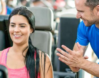 Trainer encourages woman on gym machine