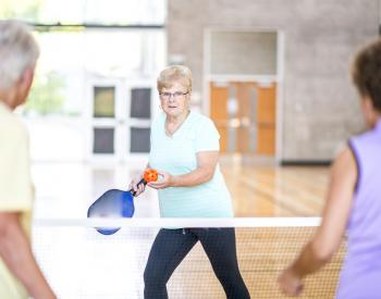 Older woman serves whiffle ball