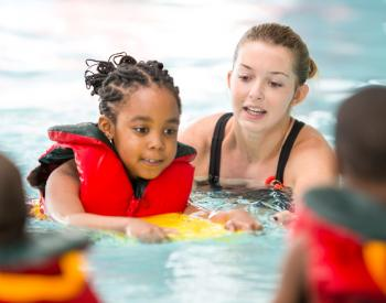 Woman helps young girl in life vest in pool
