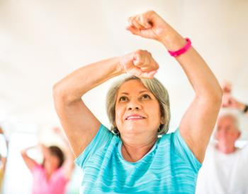 Older woman lifts arms above head in class