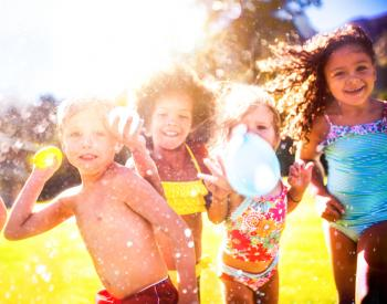 Group of young children toss water balloons