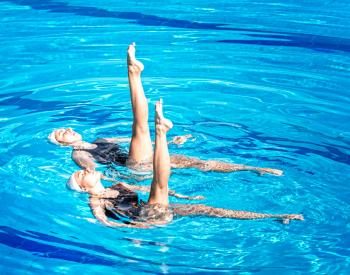 Two women perform synchronized swim routine