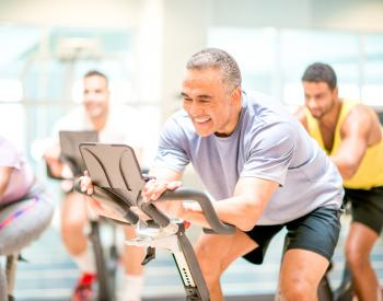 Smiling man uses exercise bicycle