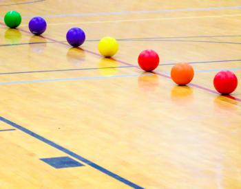 Line of colorful dodgeballs on gym floor
