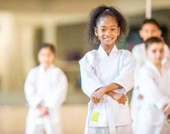 Smiling girl practices martial arts in class