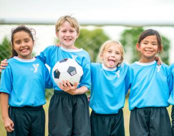 Group of children in blue holding soccer ball