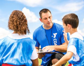 Man speaks to young children in sports gear