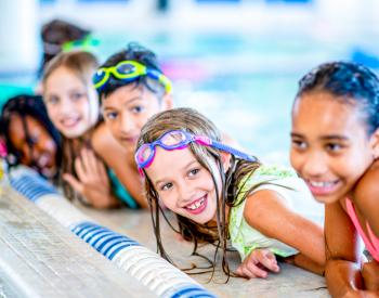 Smiling children lean out of pool