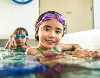Young girl in goggles holds edge of pool