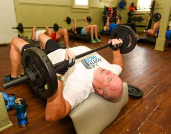 Man lifts weight from chest at gym