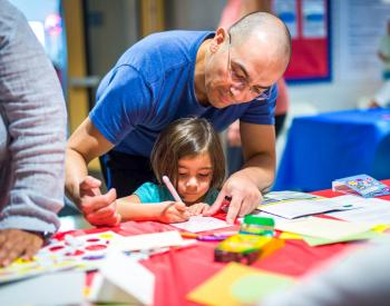 Volunteer helps young child with art