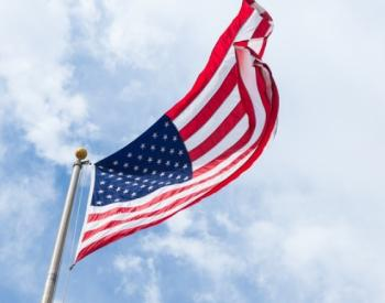 American flag on flagpole against cloudy sky