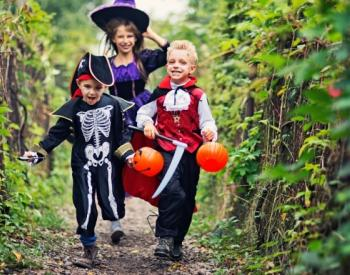 Kids in Halloween costumes run down grassy path