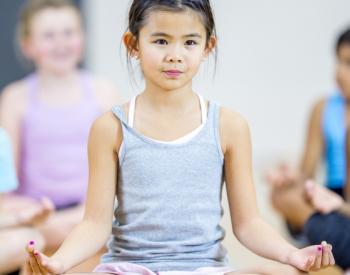 Young girl sits at front of group doing yoga