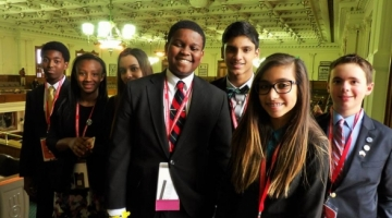 A group of young adults stand in a group proudly representing Youth and Government
