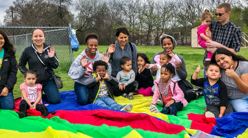 A group of caregivers and children sit next to a colorful parachute outside
