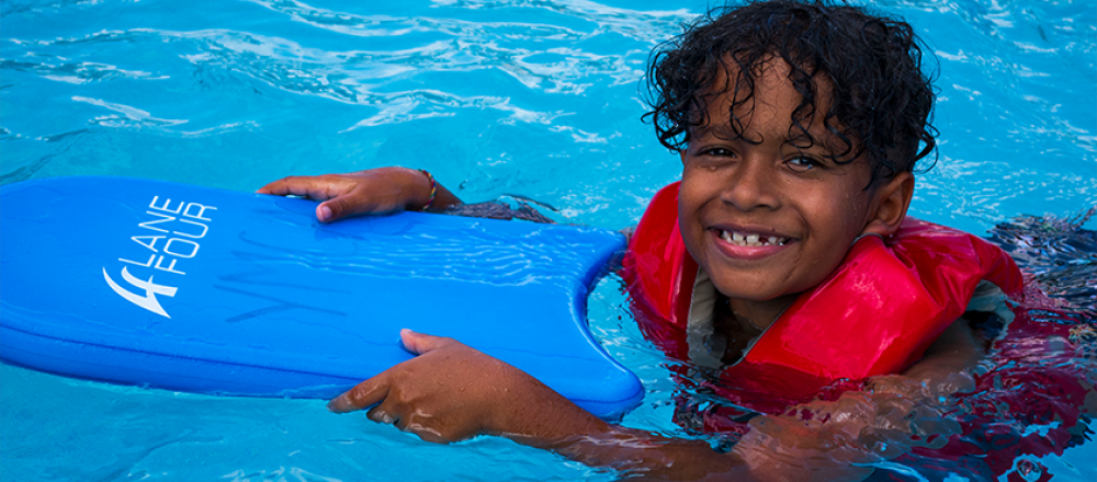 smiling boy swimmer in the water holding a kickboard