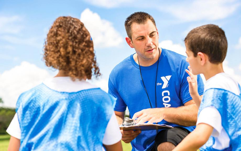 Y coach talks to kids on sports field