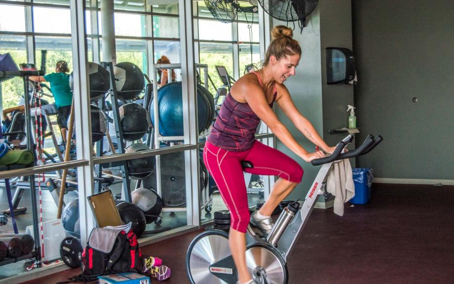 Woman uses exercise bike in gym