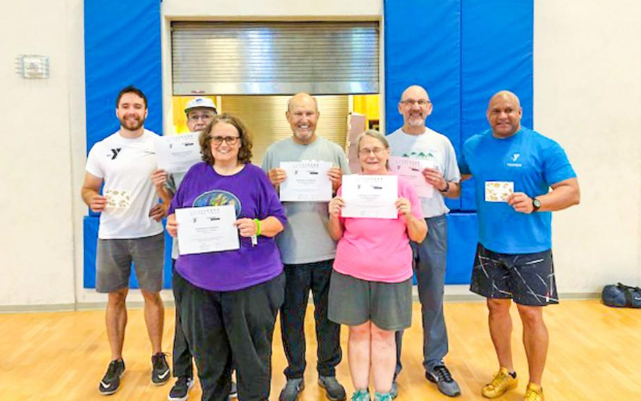 Group holding certificates stand in gym