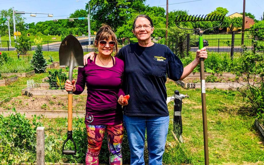 Two women stand in front of garden with shovel and rake