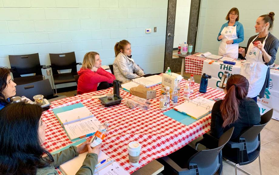 YMCA volunteers sit around table with checkered tablecloth