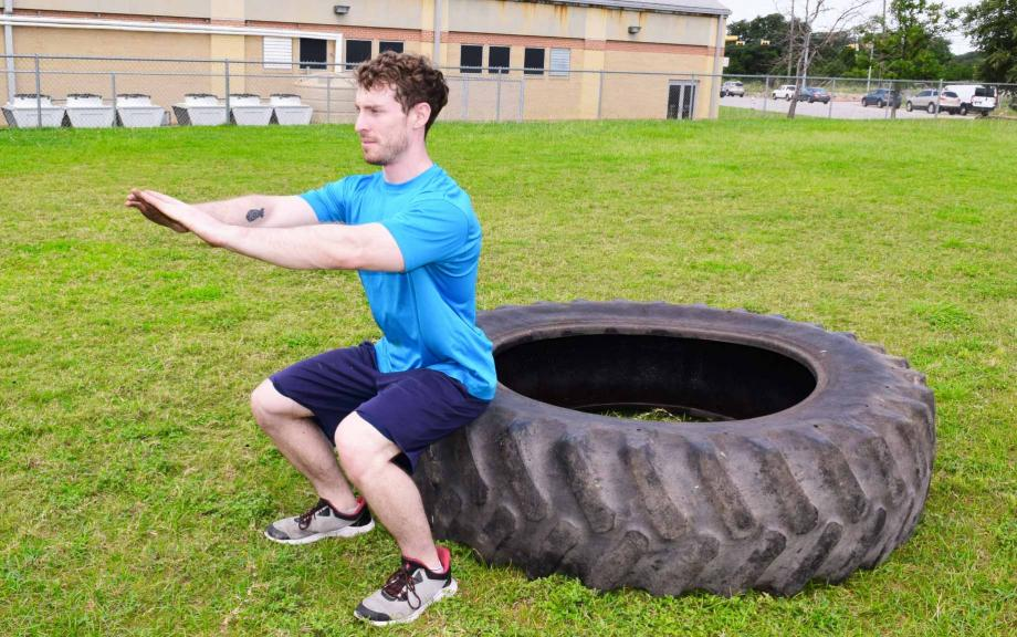 Man does a squat against a large tire