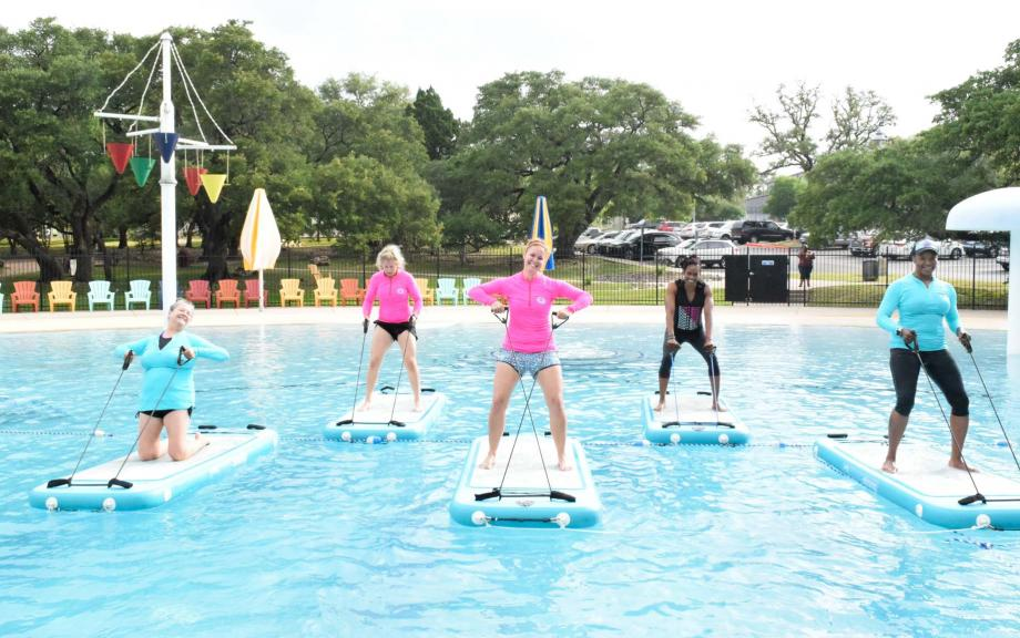 Women stand on floating pool boards for aquafit class