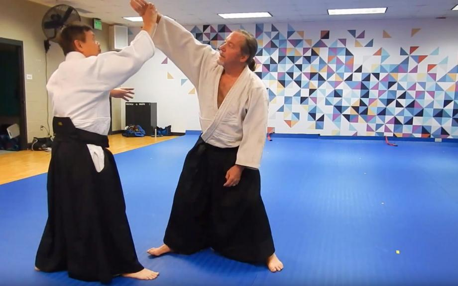 Two men do martial arts in traditional outfits