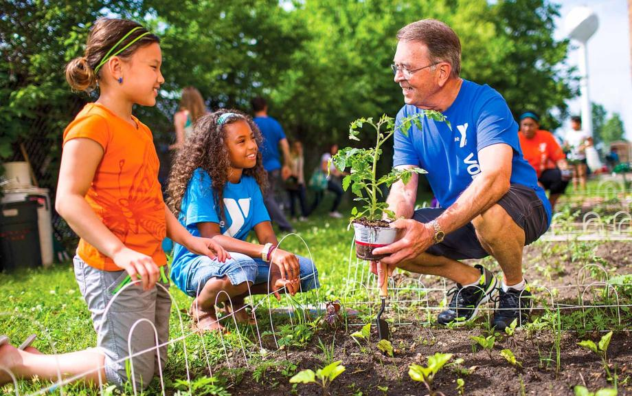 Volunteer works with kids in garden