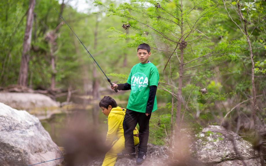 Kids use fishing rods in river
