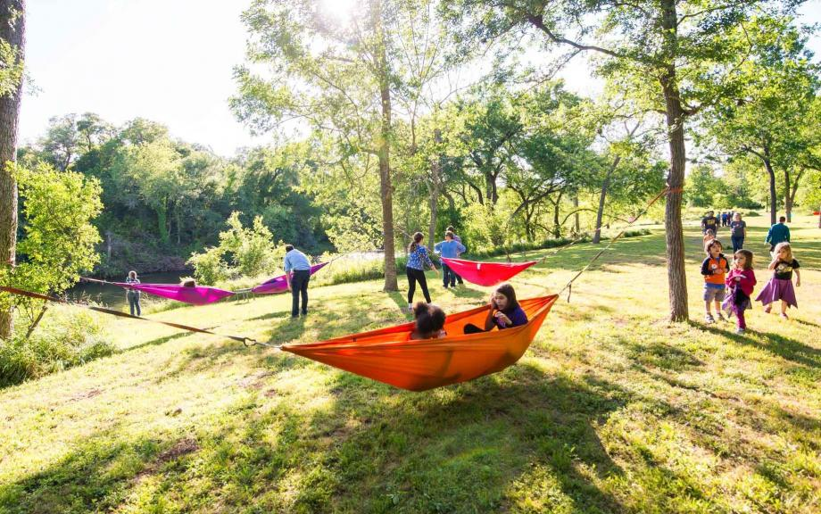 People enjoy colorful hammocks hung in field