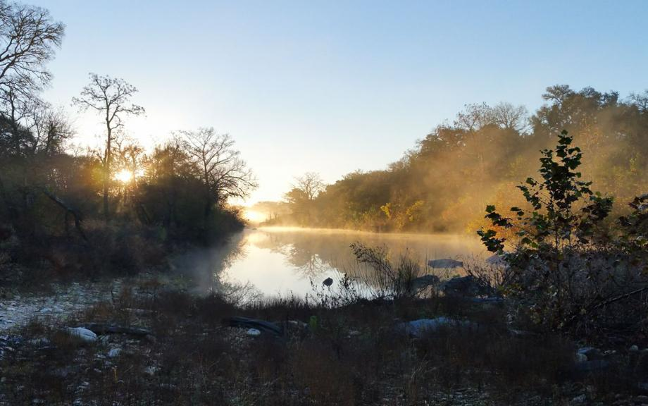 Mist rises from river at sunrise